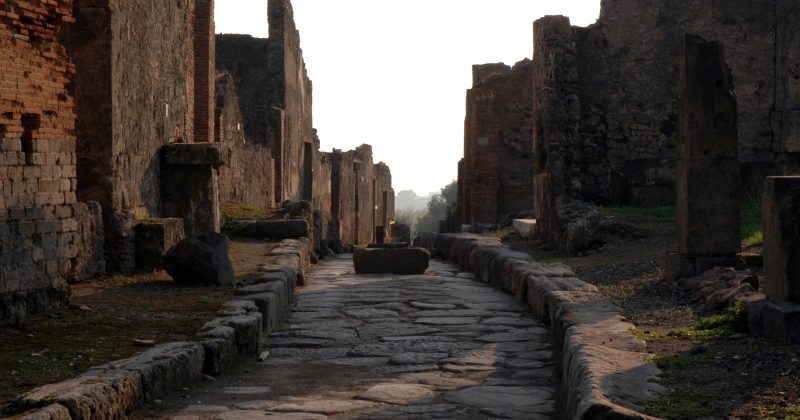"""Looking up a house-lined, stone-paved street of the ancient ruined Roman city of Pompeii."""